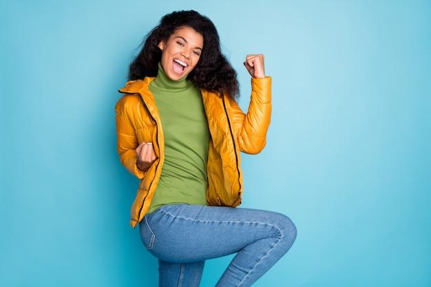 サッカーの試合のゴールを祝う驚くべき面白い暗い肌の巻き毛の女性トレンディな黄色の春のオーバーコートジーンズ緑のプルオーバー孤立した青い色の壁