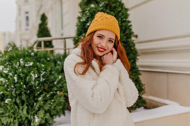 トウヒの横に笑顔でポーズをとる素晴らしい生姜の女の子。トレンディなコートを着たインスピレーションを得た白人女性の屋外写真。