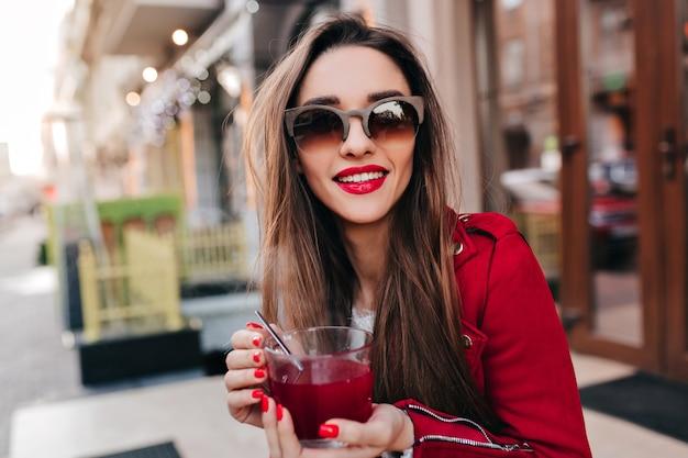 Incredibile ragazza in occhiali da sole marroni, bere il tè con il sorriso