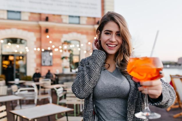 Incredibile ragazza in abito grigio casual che beve cocktail dolce nel ristorante all'aperto in una giornata fredda