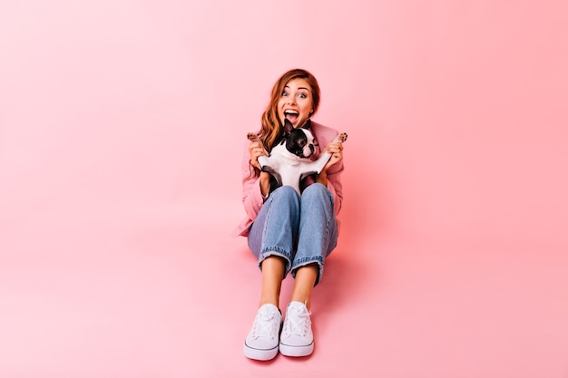 犬と遊ぶカジュアルな白い靴の素晴らしい女の子。フレンチブルドッグの子犬とのポートレート撮影中に笑っている感情的な生姜の女性の肖像画。