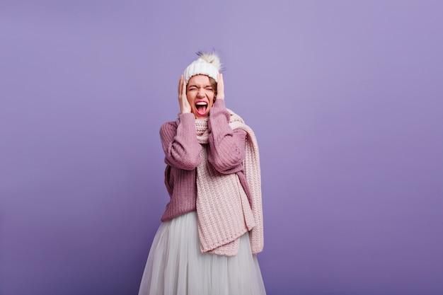 目を閉じて叫んでいる長いニットのスカーフの素晴らしい女の子。紫色の壁にポーズをとってスタイリッシュな冬の服を着た壮大なヨーロッパの女性