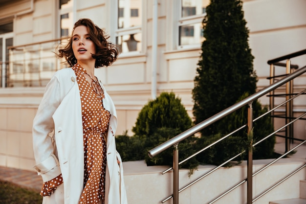目をそらしている長い白衣の素晴らしい女の子。通りに立っている快活な官能的な女性の屋外ショット。