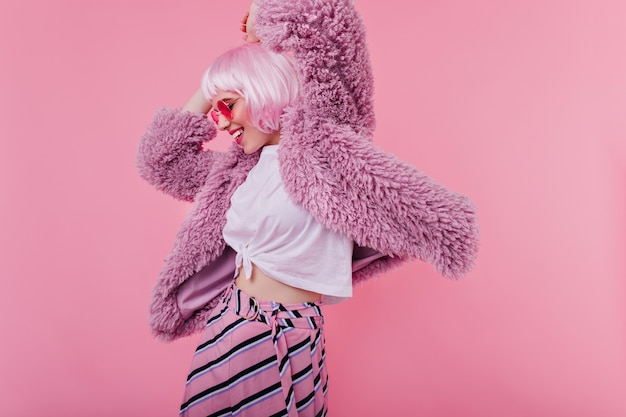 Удивительная девушка в фиолетовой куртке развлекается во время фотосессии в помещении. милая женская модель в солнцезащитных очках и розовом перуке танцует и смеется
