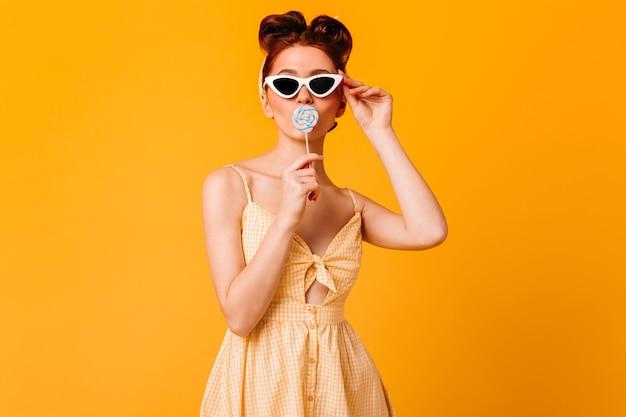 롤리팝을 핥는 선글라스에 놀라운 소녀. 노란 공간에 고립 된 생강 핀 업 여자의 스튜디오 샷.