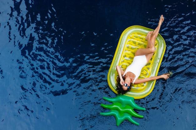 パイナップルのマットレスの上に横たわっているサングラスの素晴らしい女の子。プールでリラックスした水着姿の素敵な日焼けした女性モデルの屋外写真。