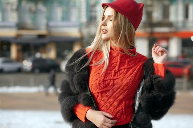 スタイリッシュな赤いキャップとニットのスカーフを身に着けている素晴らしい女の子