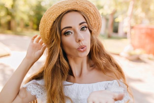 晴れた朝に屋外でポーズをとっている間、空気のキスを送る大きな緑色の目を持つ素晴らしい女の子。良い日と太陽の光を楽しんでいる流行の麦わら帽子の素敵な若い女性の肖像画。