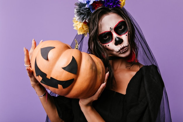 Amazing girl with black bridal veil isolated on purple wall. indoor photo of evil lady in zombie attire holding halloween pumpkin.