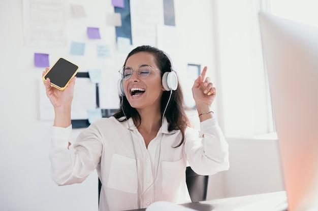 Удивительная девушка с каштановыми волосами веселится в офисе, слушая музыку в белых наушниках