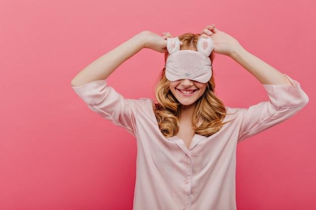 巻き毛の素晴らしい女の子は、週末の朝にアイマスクを着用して笑っています。ピンクの壁に浮かんでいるシルクのナイトスーツの至福の白い女性モデル。
