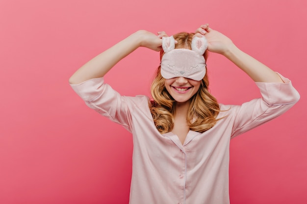 Incredibile ragazza con i capelli ricci indossa la maschera per gli occhi e ride nella mattina del fine settimana. beata modella bianca in abito da notte di seta che scherza sul muro rosa.