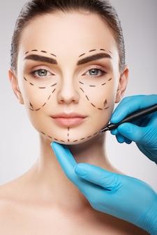 Удивительная девушка с темными бровями на фоне студии, руки доктора в синих перчатках, рисуя линии перфорации на лице, концепция пластической хирургии.