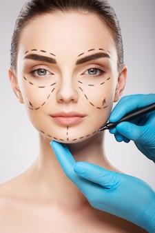 Amazing girl with dark eyebrows at studio background, doctor's hands wearing blue gloves drawing perforation lines on face, plastic surgery concept.