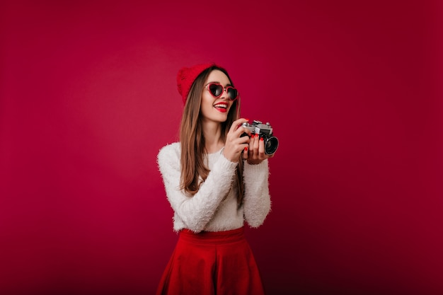 Claret 공간으로 포즈를 취하는 우아한 빨간 매니큐어와 놀라운 소녀