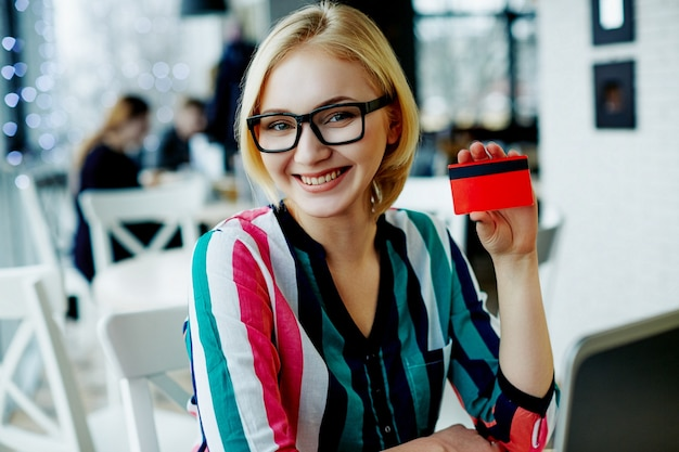 Amazing girl with light hair wearing colorful shirt and glasses sitting in cafe with laptop and credit card, freelance concept, online shopping, smiling.