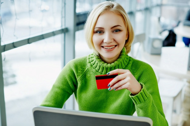 Amazing girl with light hair wearing green sweater sitting in cafe with laptop and credit card, portrait, freelance concept, online shopping.