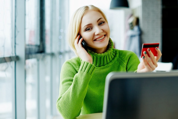 노트북 및 신용 카드, 초상화, 프리랜서 개념, 온라인 쇼핑으로 카페에 앉아 녹색 스웨터를 입고 가벼운 머리를 가진 놀라운 소녀.