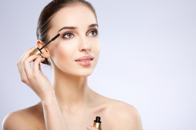 Amazing girl with nude make up posing at grey studio background, beauty photo concept, perfect skin, using mascara.