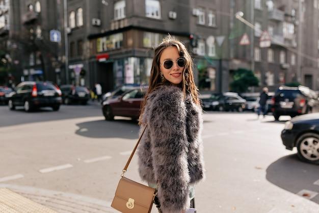 Incredibile ragazza con trucco nudo che indossa un vestito elegante autunno che cammina sulla città soleggiata