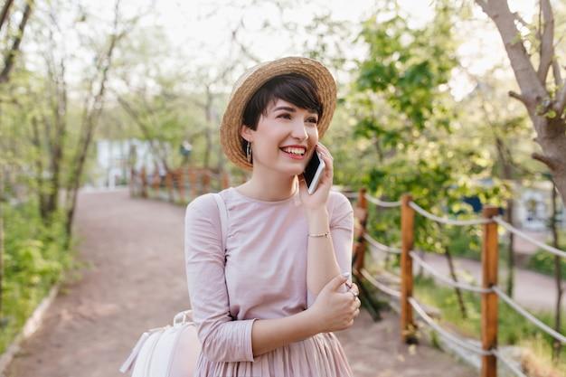 電話で話し、笑顔で見上げる短い黒髪の素晴らしい女の子