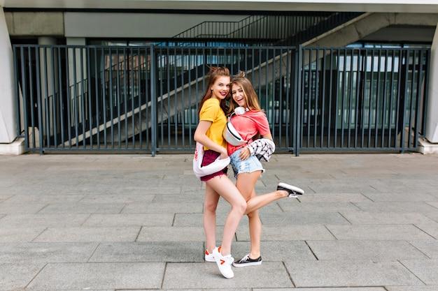 Incredibile ragazza con il sorriso in scarpe da ginnastica bianche in posa volentieri su urbano vicino a ballare amico biondo in camicia rosa