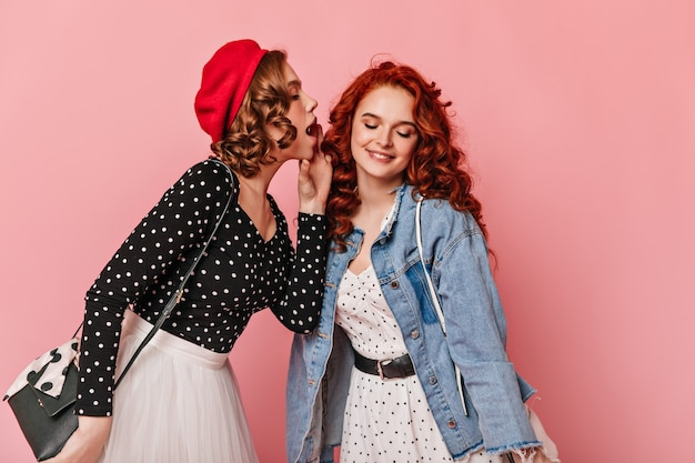 ピンクの背景に秘密を共有する素晴らしい女の子。トレンディな服を着て話す女性のスタジオショット。