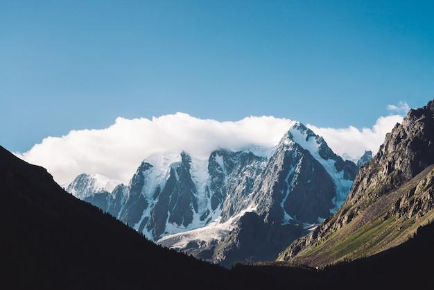 Изумительный ледник под голубым небом. горный хребет со снегом. огромное облако на гигантских чудесных снежных горах. атмосферный минималистичный угрюмый пейзаж величественной природы высокогорья в матовых тонах.