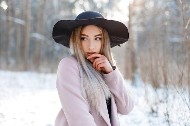 겨울 공원에서 화창한 날에 포즈를 취하는 세련된 핑크 따뜻한 코트에 고급스러운 검은 모자에 놀라운 매력적인 꽤 아름다운 젊은 여자. 산책에 섹시 한 유행 소녀입니다.