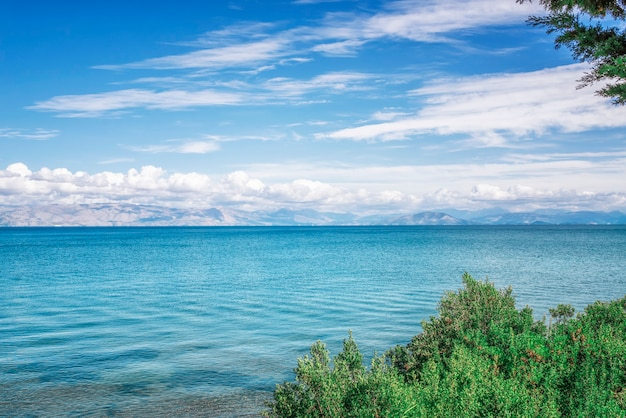 Amazing green bay with crystal clear water, big stones on corfu island, greece. beautiful landscape of ionian sealine. sunny weather, blue sky.