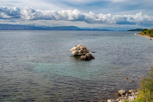맑은 물, 코르푸 섬, 그리스의 큰 돌으로 놀라운 그린 베이. 이오니아 바다 해변의 아름다운 풍경입니다. 화창한 날씨, 푸른 하늘.