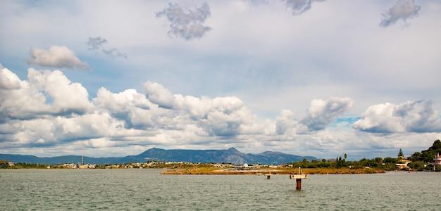 Изумительная зеленая песчаная бухта с кристально чистой водой и большими камнями на острове корфу.