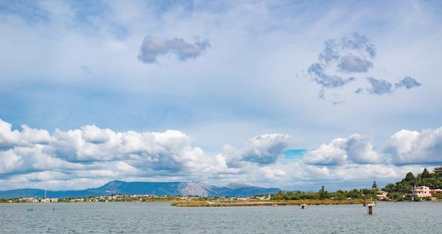 맑은 물, 코르푸 섬, 그리스에 큰 돌과 놀라운 녹색 모래 베이. 이오니아 바다 해변의 아름다운 풍경입니다. 화창한 날씨, 푸른 하늘. 프리미엄 사진