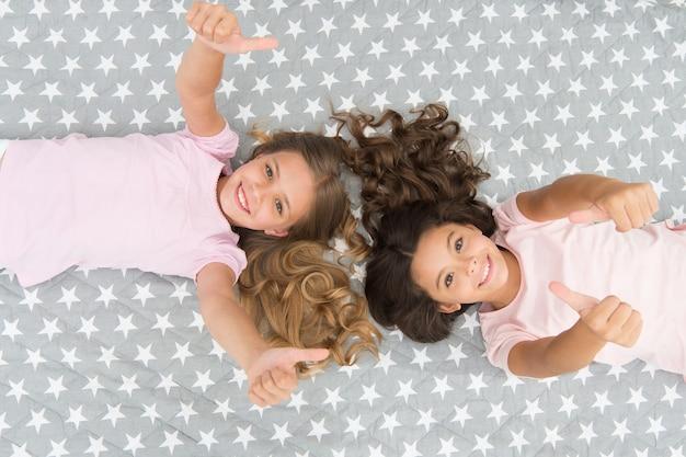 素晴らしい髪のヒント。リラックスした子供たちの巻き毛の髪型。コンディショナーマスクオーガニックオイルが髪をツヤと健康に保ちます。翌朝でも髪をカールさせてください。長い髪の女児はベッドの上面図に横たわっていた。