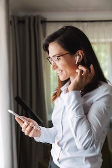 電話を使用してイヤホンで音楽を聴いて携帯電話で話している自宅の屋内で正装の服を着た驚くべき幸せな美しい若いビジネスウーマン。
