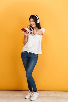 ヘッドフォンで音楽を聴く驚くべき幸せなかわいい若いきれいな女性は、平和のジェスチャーを作ります。