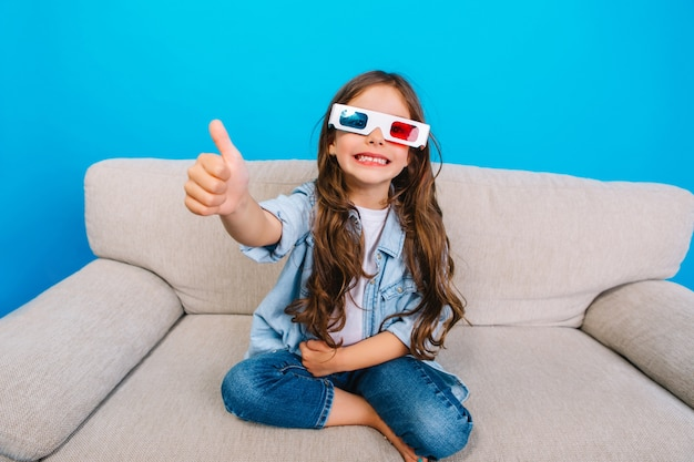 Amazing happy little girl in 3d glasses with long brunette hair smiling to camera on couch isolated on blue background. showing true positive emotions, happy childhood of fashionable kid