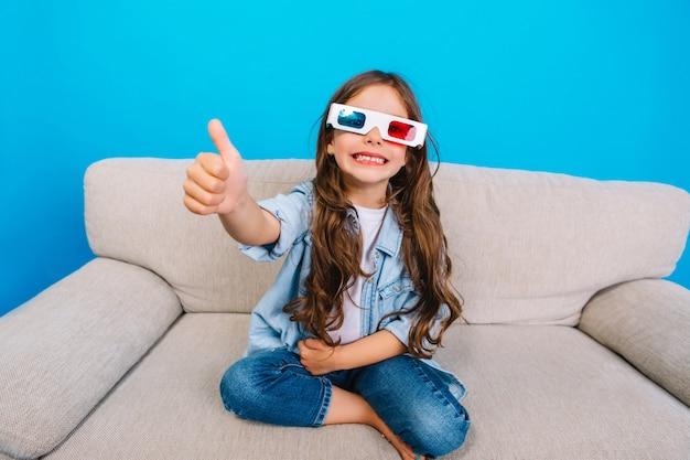 파란색 배경에 고립 된 소파에 카메라에 웃 긴 갈색 머리를 가진 3d 안경에 놀라운 행복 한 어린 소녀. 진정한 긍정적 감정, 세련된 아이의 행복한 어린 시절을 보여줍니다.