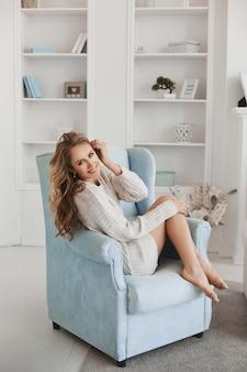 Изумительная радостная модельная девушка с длинными светлыми волосами усмехаясь пока сидящ в кресле в современной белой квартире. веселая молодая женщина в вязаном белом свитере и с голыми ногами