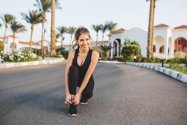 晴れた朝に路上で実行する準備をして体操で素晴らしいうれしそうな若い女性。笑顔、アクティブなライフスタイル、スニーカーに靴ひもを結ぶ、ポジティブな表現、ワークアウト