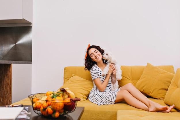 モダンなアパートメントのソファーに犬と一緒に身も凍るようなドレスでブルネットの髪をカットで素晴らしいうれしそうな若い女性。楽しんで、家のペット、喜び、家の快適さ、居心地の良い、レジャー、週末