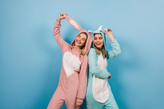 Восхитительные дамы в забавных пижамах, выражающие искренние эмоции
