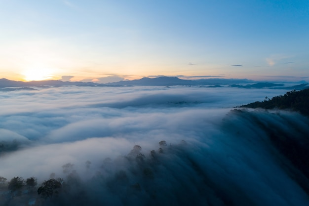 Amazing landscape light nature scenery view, beautiful light sunrise or sunset over tropical sea and foggy mist on mountains peak in thailand aerial view drone camera shot high angle view.