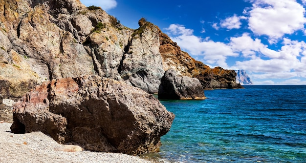 Удивительный пейзаж на берегу синего океана в ясную солнечную погоду. скала удара линии ресниц морских волн на пляже. уютные фоны для сайта или обои большого разрешения. концепция релаксации, отдыха