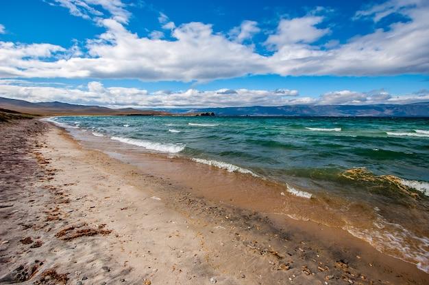 Удивительный пейзаж с лазурной водой и песчаным берегом на байкале. ветрено и волны на озере. горы на горизонте. облака на голубом небе. по горизонтали.