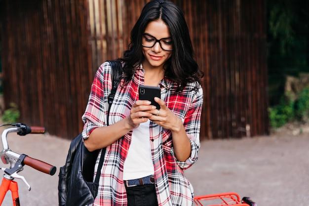 誰かを待っている間電話スクリーンを見ている驚くべきラテン女性モデル。赤い自転車の近くに立っている素敵なブルネットの女性の屋外の肖像画。