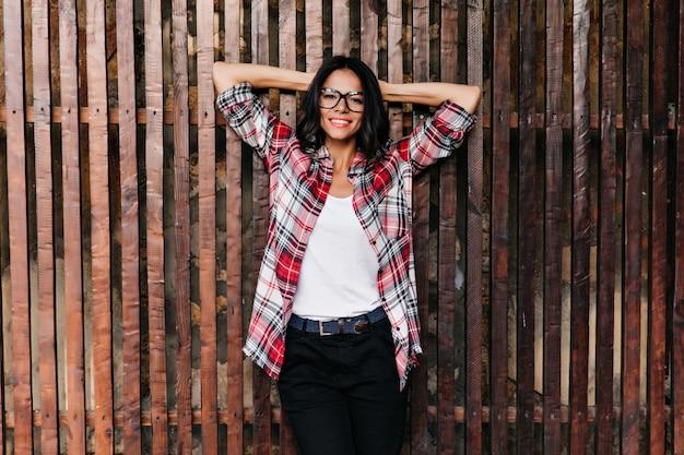 손으로 나무 벽에 서있는 놀라운 웃는 소녀. 행복을 표현하는 debonair 라틴 여자의 야외 사진
