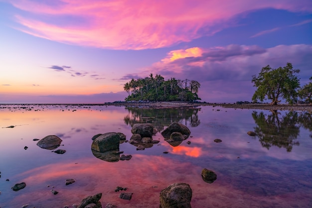 Amazing light sunset sky over small island in tropical sea sunset or sunrise time at low tide day with rocks in the foreground beautiful nature landscape seascape.