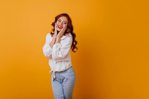 노란색 벽에 웃 고 놀라운 긴 머리 여자. 하얀 스웨터에 포즈를 취하는 화려한 생강 여성 모델.