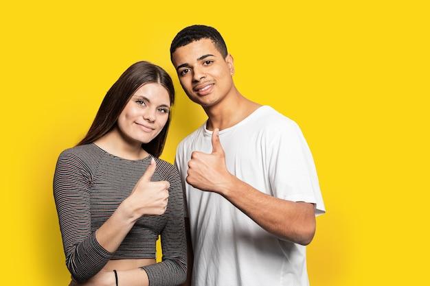 Удивительная супружеская пара, показывающая символы ок, согласна с хорошим качеством продукта, носить повседневную одежду, изолированный желтый